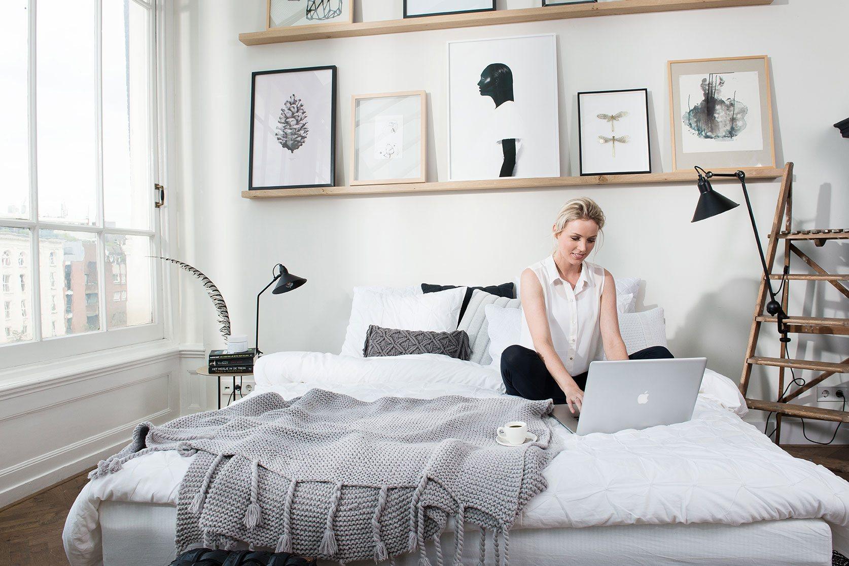 vrouw met laptop werkend op bed